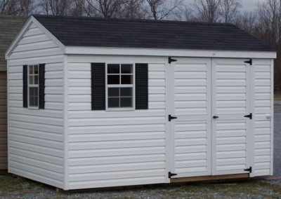 A white vinyl shed with a black shingled, a-roof style roof. Shed is 8x12 and has a double doors and two windows