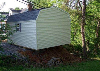 12 x 16 V-High Barn with almond siding, white trim, estate gray shingles and gray shutters