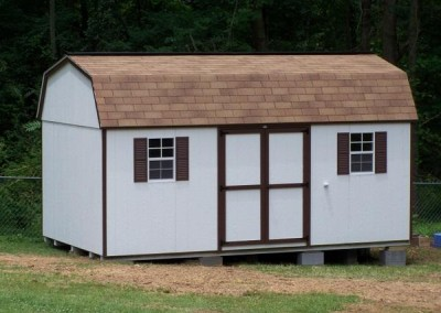 A white painted high barn shed with a shingled, barn style roof. Shed has brown trim and a set of solid double doors.