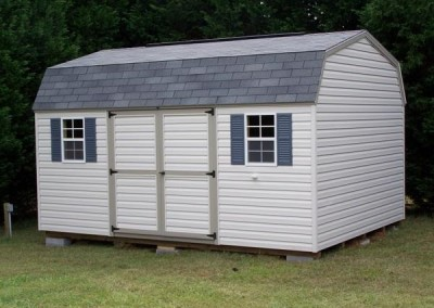A vinyl shed sized 10x14. The roof is barn style and is shingled. Shed has a set of double doors and two windows with shutters