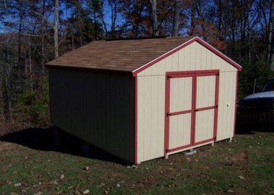 A 12x16, painted shed with a shingled a-roof style roof. Shed has red trim and no windows. Shed has a set of double doors