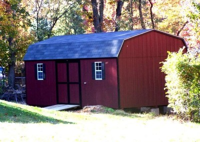 A 12x24 painted high barn shed with a shingled, barn style roof. Shed has a ramp, a set of double doors, and two windows with shutters