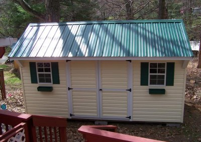 A 10x16 vinyl shed with a metal, carriage style roof. Shed has two windows with green shutters and flower boxes. Shed has a set of double doors