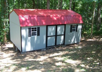 A painted shed a high barn style roof. Shed has red metal roofing and a set of double doors.