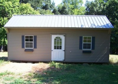 A 12x24 sized vinyl shed with a carriage style metal roof. Shed has two windows with shutters and flower boxes. The shed has a fiberglass, circle too house door.