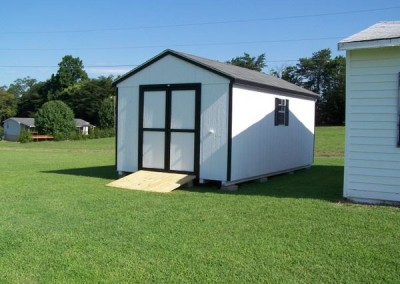 A white painted shed with a black shingled, a-roof style roof. Shed has black trim, a solid double door, two windows with black shutters, and a treated wooden plank