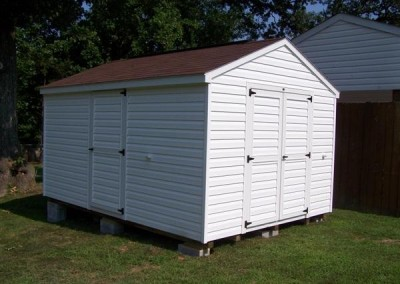 A white vinyl shed with a shingled a-roof style roof and white trim. shed has a double door on gable end and a 3 foot vinyl door on side