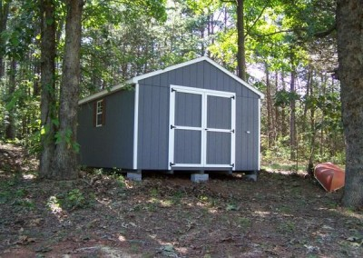 A 12x16 painted shed with an a-roof style shingled roof. The shed has two windows and a set of double doors