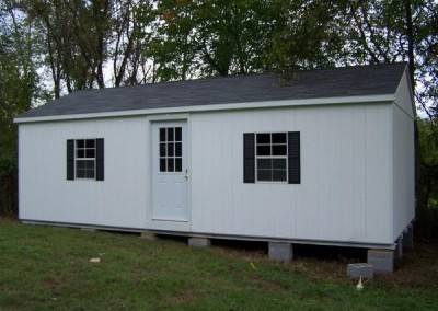 A 14x28 sized painted shed with an A-roof style, shingled roof. Shed has a house door with a window and two windows with shutters