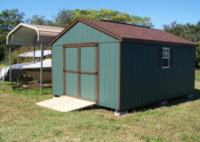 A 12x16 sized green shed with brown shingles and trim. Shed has a-roof style roof, a set of double doors, two windows with shutters, and a treated wooden ramp