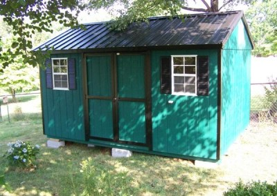 A 10x14 painted shed with black trim. Shed has a black metal, a-roof style roof and a set of double doors as well as two windows with black shutters