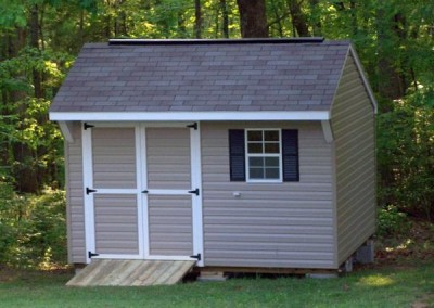 10 x 12 V-Carriage with clay siding, white trim, driftwood shingles, and black shutters