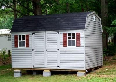 10 x 14 V-High Barn with flint siding and trim, black shingles, and redwood shutters