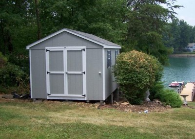 A 10x14 grey painted shed with white trim. The shed has a shingled, a-roof style roof, two windows with shutters, and a solid double door