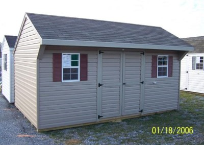 A vinyl 10x16 shed with a shingled carriage style roof. Shed has a set of double doors and two windows with shutters