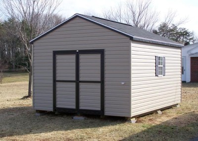 A vinyl shed with an a-roof style, shingled roof. Shed has a 6 foot wide double door on gable end and a window on either side of shed