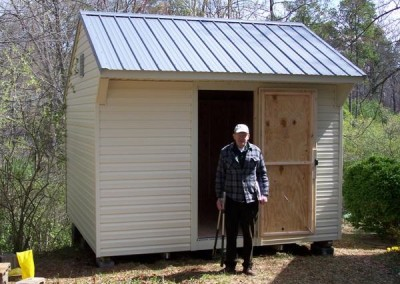 A white vinyl, 12x12 shed with a metal carriage style roof. Shed has a gable vent and one 3 foot wide door