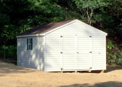 12 x 16 V-A-roof with ivory siding and trim, brownwood shingles and forest green shutters