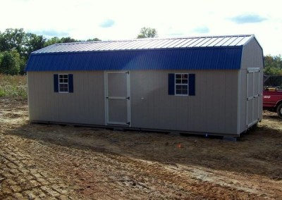 12 x 28 Painted High Barn painted tan with almond trim, ocean blue metal roof and bedford blue shutters