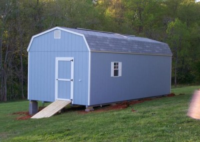 12 x 28 Painted High Barn painted blue with white trim, aspen gray shingles, white shutters, ridgevent, gable vents, skylight, and singe door