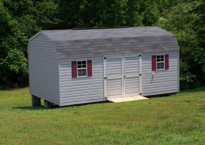 12 x 20 V-High Barn with gray siding, white trim, estate gray shingles and maroon shutters, and a treated wooden ramp