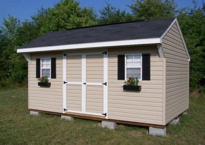 A vinyl 10x16 shed with a shingled a-roof style roof. Shed has a shingled carriage style roof and two windows with black shutters and flowerboxes. Shed has a double door
