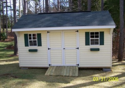 10X16 V-Carriage shed with green shutters and flower boxes. Shed has a double door and two windows with a wooden ramp