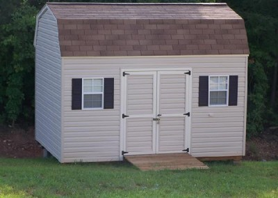A vinyl 10x14 shed with a set of double doors and two windows with shutters. Shed has a ridge vent and a treated wooden ramp. The roof is barn style and shingled