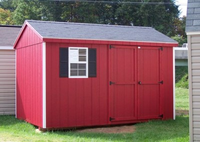 A red painted 8x12 shed with a shingled roof. Shed has one window with shutters and a solid double door.
