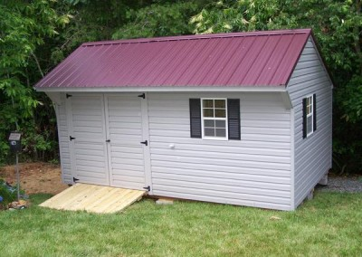 10 x 16 V-Carraige with flint siding and trim, burgundy metal roof and black shutters