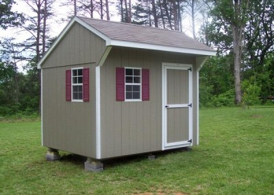 An 8x10 painted shed with a shingled carriage style roof. Shed has a single painted door and two windows with shutters