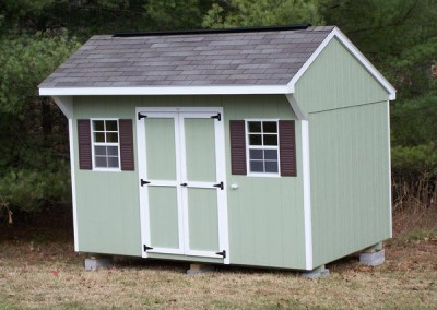 A light green painted shed with a shingled, carriage style roof. Shed has a set of double doors and two windows.