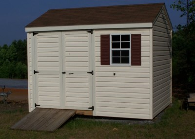 A 8x10 vinyl shed with a shingled, a-roof style roof. Shed has a set of double doors, a window with shutters, and a wooden ramp
