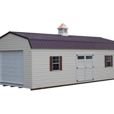 A long vinyl shed with a metal, high barn style roof. The shed has a garage door at one end, a cupola on roof, a 6 foot wide set of GGS doors with transom windows, and two shed windows with shutters