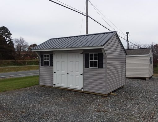 10 x 14 size vinyl carriage style shed with flint siding, white trim, black metal roof, black shutters, 6 foot fiber doors with two windows