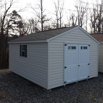 12 x 16 size vinyl a-roof style shed with pearl/ivory siding, white trim, driftwood architectural shingle roof, forest green shutters, 12' workbench, 10' ridgevent, 6 foot transom fiber doors with two windows