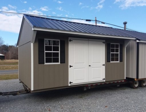 """10 x 16 size painted carriage style shed with black metal roof and 6 foot fiber 2 plank double doors with two windows 24"""" x 36""""."""