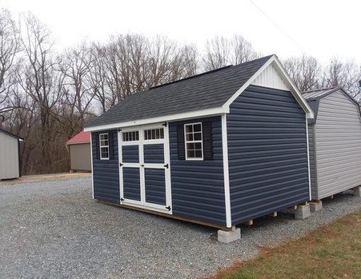 10 x 16 size vinyl garden style shed with dark blue custom color siding, white trim, black architectural shingle roof, black shutters, 10' ridgevent, l p pro struct flooring, 6 foot ggs transom doors, with two windows.