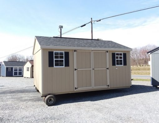 12 x 16 size painted a-roof style shed with tan siding, tan trim, black architectural shingle roof, black shutters, 10' ridgevent, ggs 6 foot doors with two windows, silver tech smart siding.