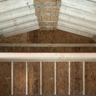 A completed wooden loft under barn style shed roof