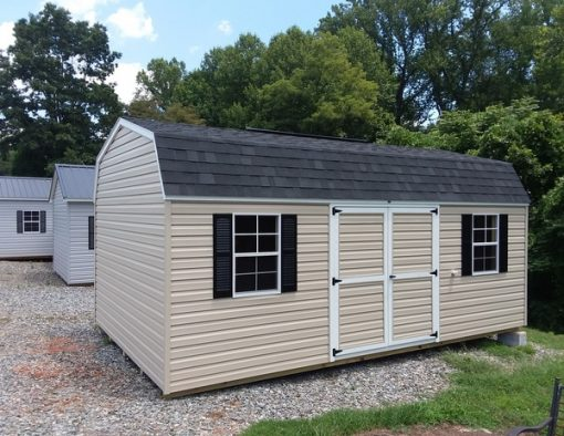 12 x 20 size vinyl high barn style shed with tan siding, white trim, black architectural shingle roof, black shutters. (2) 12' lofts, 8' ridgevent, 6 foot good's garden sheds double doors, two windows.