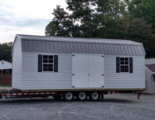 12 x 24 size vinyl high barn style shed with gray siding, white trim, charcoal metal roof, black shutters. (2) 12' lofts, (1) 12' workbench, tech shield radiant barrier on the walls, l p pro struct flooring, 6 foot fiber doors, with two windows.