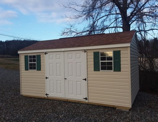 10x16 size vinyl a-roof style shed with almond siding, white trim, desert tan arch shingle roof, green shutters, 8' ridgevent and 6 foot fiber doors with two windows