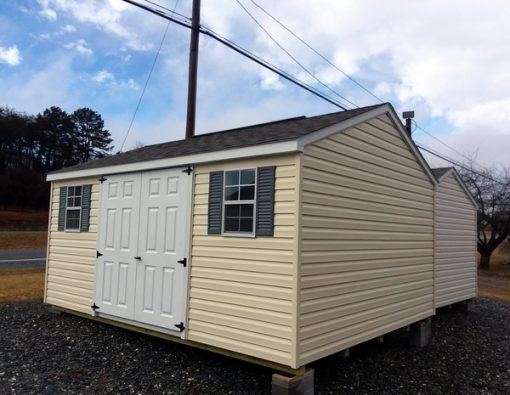 12x16 size vinyl a-roof style shed with cream siding, white trim, driftwood arch shingle roof, slate blue shutters, 8' ridgevent and 6 foot fiber doors with two windows
