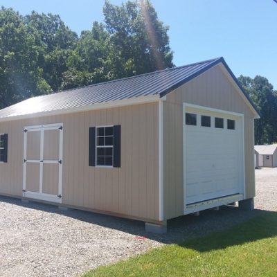 14 x 28 size painted classic garage style shed with leola almond siding, white trim, black metal roof, black shutters, 1 14' loft, 1 14' workbench lp pro struct flooring, garage door with glass, ggs 6 foot doors, two windows.