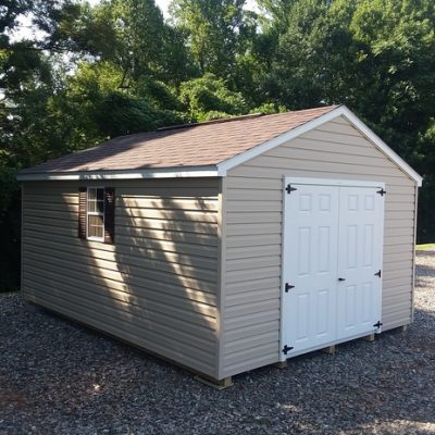 12x16 size vinyl a-roof style shed with tan siding, white trim, brownwood architectural shingle roof, brown shutters. Has 8' ridgevent, 6 foot fiber double doors and two windows.